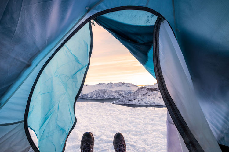 Low section of person in tent on snowcapped mountain against sky