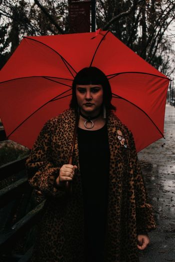 Portrait of young woman with umbrella standing in rain
