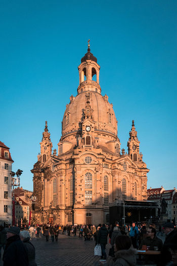 People at dresden frauenkirche against clear blue sky