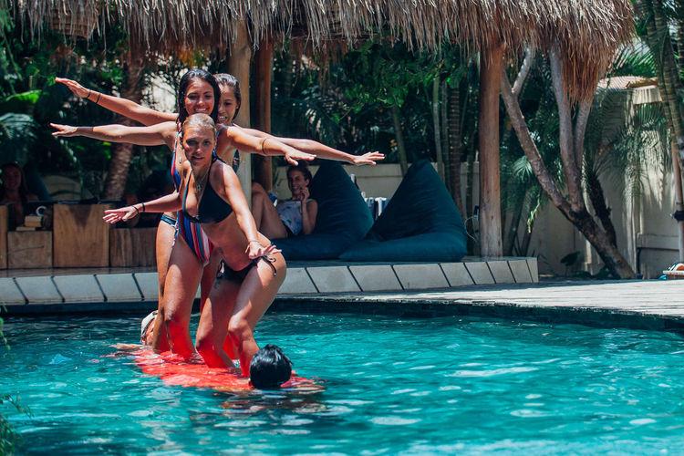 Women standing on surfboard in swimming pool