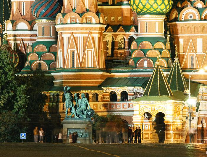 Close-up of people moving walking saint basils cathedral at night