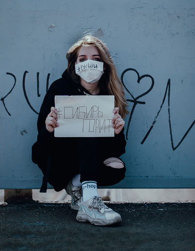 Portrait of girl with text against wall