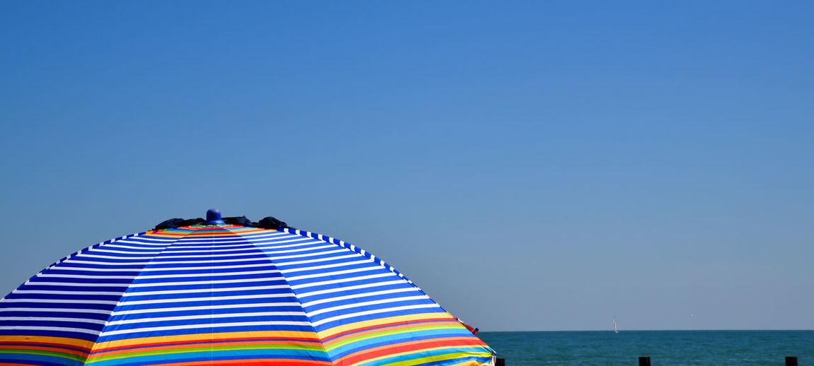 Multi colored umbrellas on beach against clear blue sky