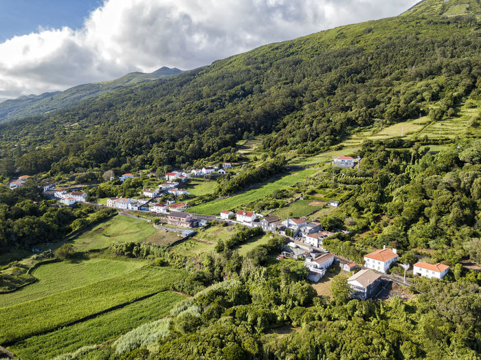 Panoramic view of green landscape and houses against sky
