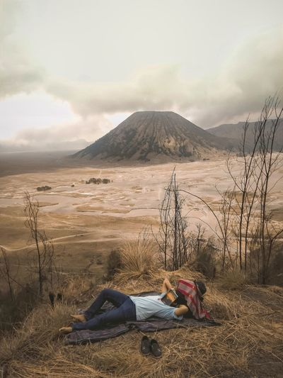 Man lying down on land against sky