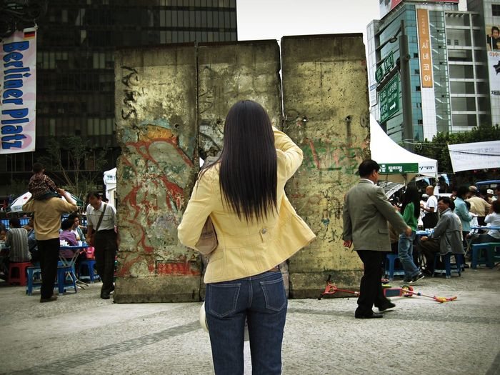 Rear view of woman standing on footpath against berlin wall