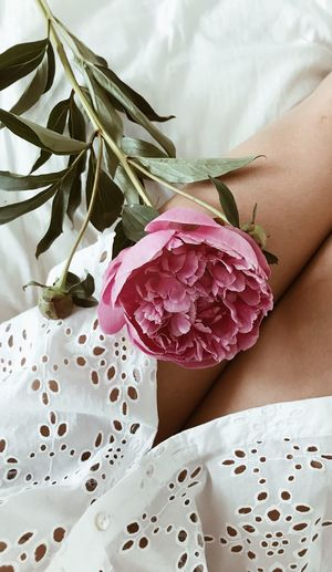 Midsection of woman with bouquet sitting on bed