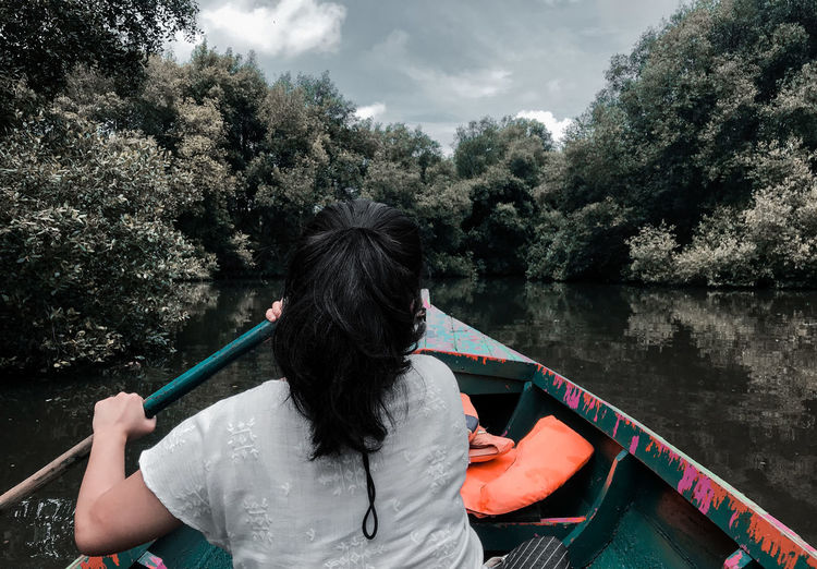 Rear view of woman on boat in lake