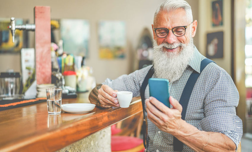 Hipster senior man using smartphone while drinking coffee Beard One Person Drink Technology Coffee Table Food And Drink Men Coffee Cup Coffee - Drink Drinking Smart Phone Mobile Phone