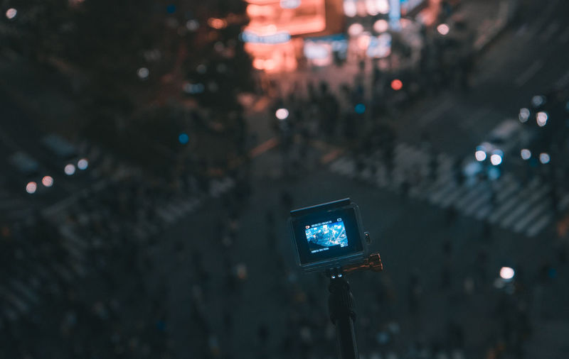 Camera on monopod over road in city at night