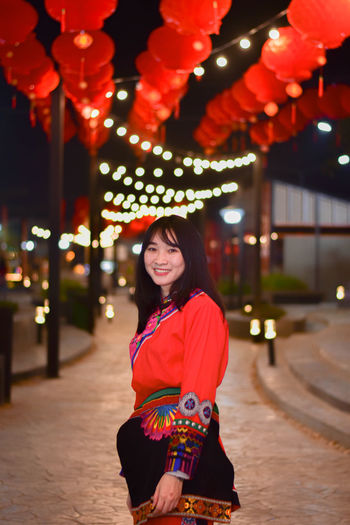 Portrait of smiling young woman standing against illuminated lights at night