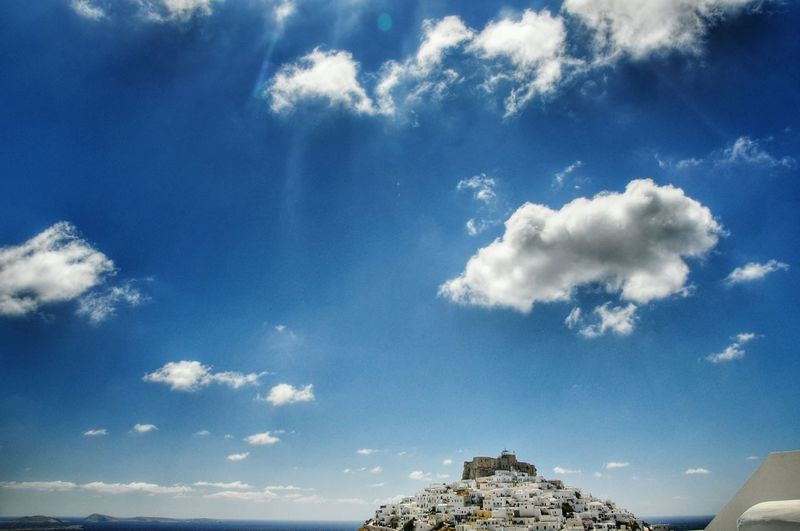 Buildings on cliff against sky at astypalaia
