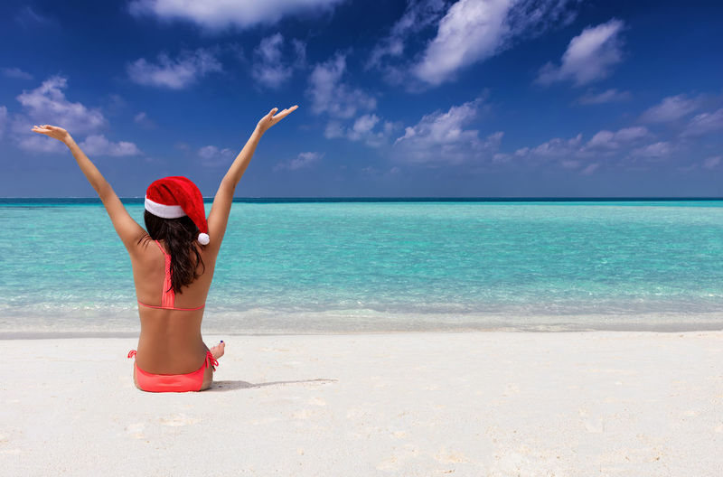 Rear view of woman wearing bikini and santa hat sitting at beach against sky