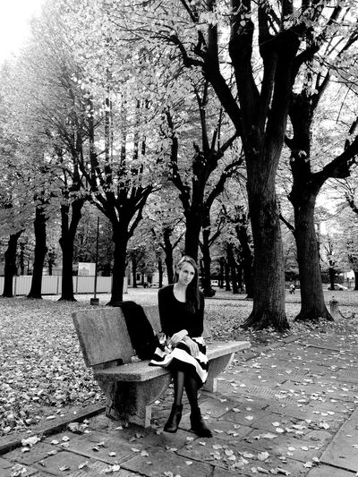 Full length of beautiful young woman sitting on bench at park