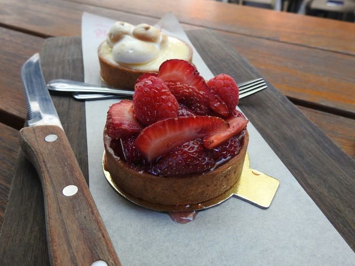 Fruit Tarts By Forks And Knife On Cutting Board At Wooden Table
