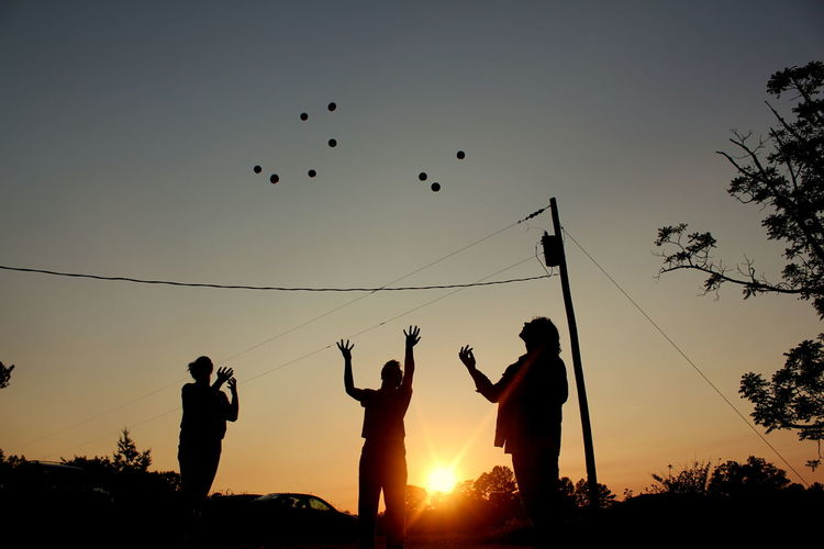 Silhouette People Juggling Balls Against Clear Sky During Sunset