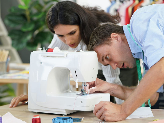 Woman looking at man putting thread in sewing machine