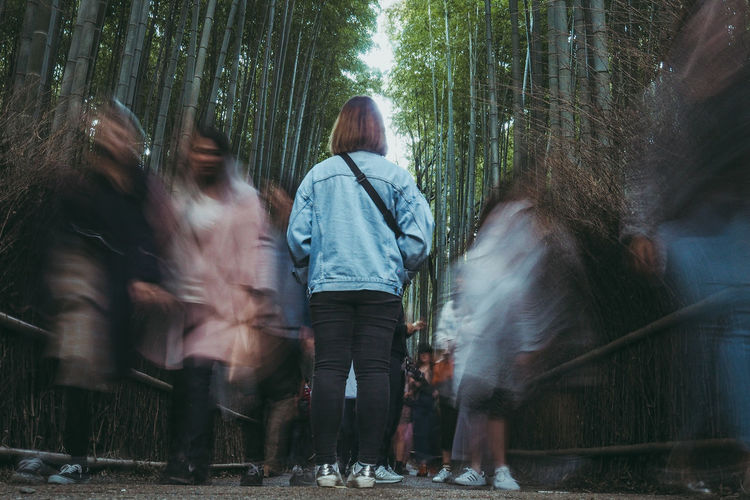 Rear view full length of woman standing on busy footpath in bamboo grove