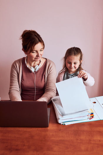 Smiling girl looking at paper on table while woman working on laptop