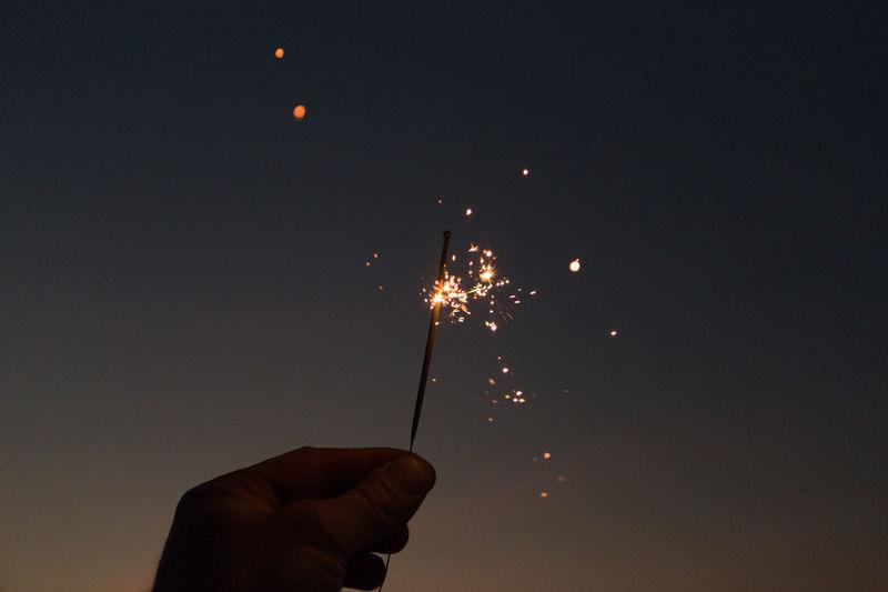 Cropped hand holding lit sparkler against sky at dusk