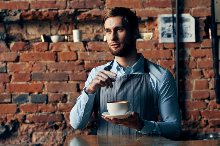 Portrait of young man drinking coffee