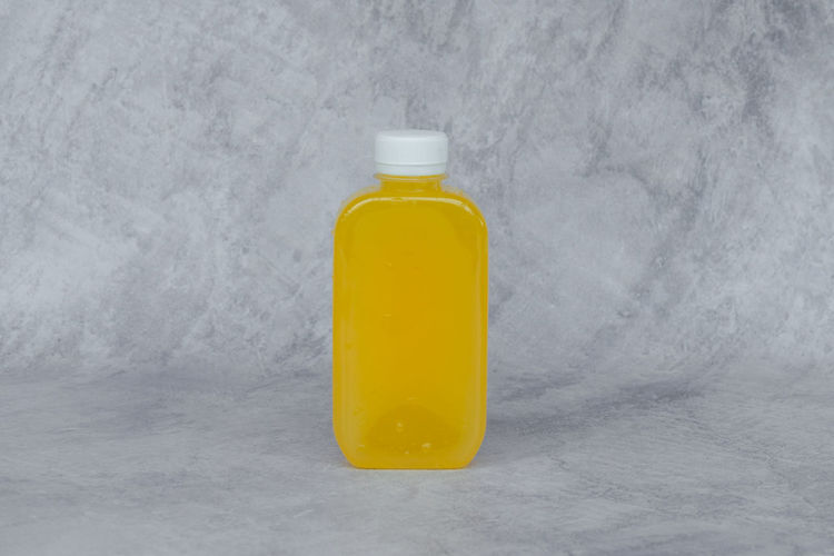 Close-up of yellow bottle on table