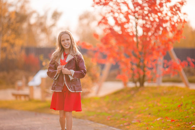 Woman with umbrella standing by autumn tree