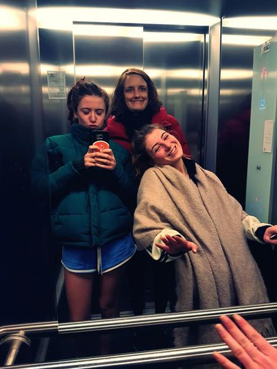 Happy friends reflecting on mirror in elevator