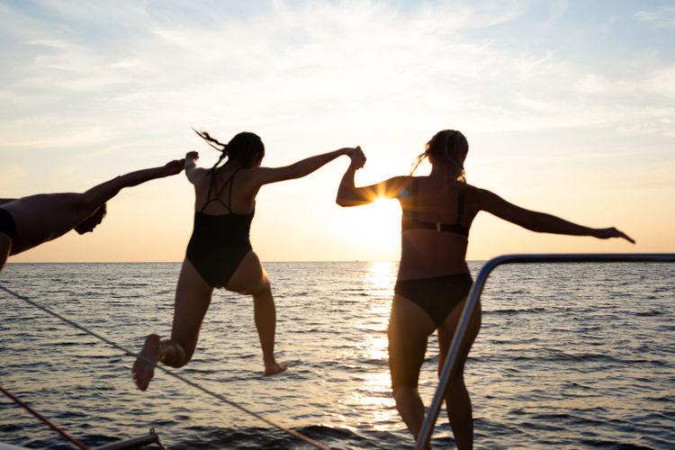 Full length of friends standing on sea shore against sky during sunset