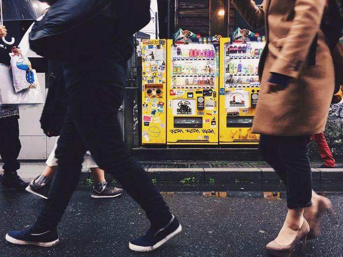 Low section of people walking in street in city