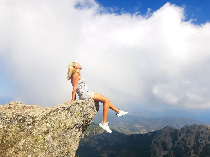 Side view of young woman on rock against sky