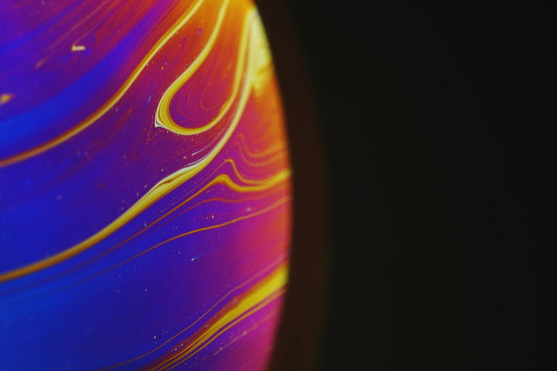 Close-up of multi colored glass against black background