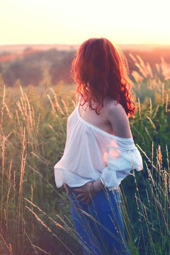 Young Woman Standing On Field During Sunset