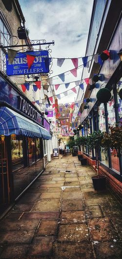 old streets Photowalktheworld Mobilephotography Oneplus6 Cotswolds Countryside Surreal Hanging Flag City Sky Architecture Built Structure vanishing point Bunting Pathway Narrow Walkway Lane The Way Forward