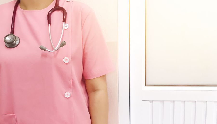 Midsection Of Female Doctor With Stethoscope Standing By Doorway