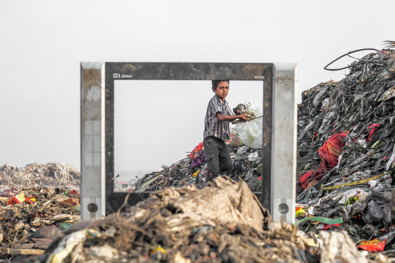 Boy standing by pile of garbage seen through metal against sky