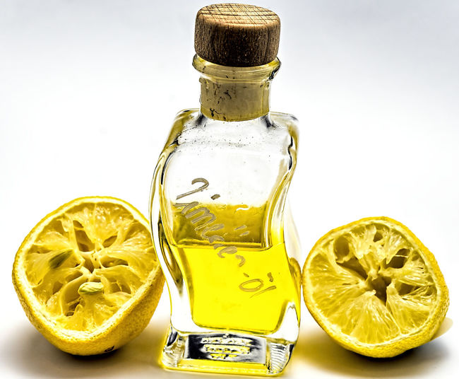 Bottle with lemon oil and two squeezed lemon halves against a white background, isolated Bottle Citrus Fruit Close-up Day Freshness Halves Indoors  Lemon No People Oil Squeeze White Background Yellow Food Stories