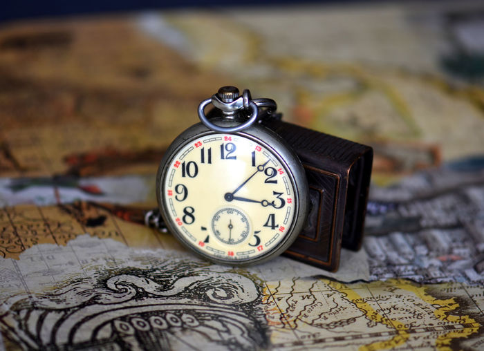 Close-up of pocket watch on map