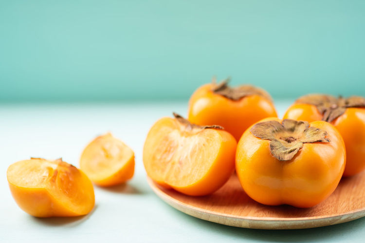 Persimmon Autumn Blue Background Close-up Colored Background Copy Space Dieting Focus On Foreground Food Food And Drink Freshness Fruit Group Of Objects Healthy Eating Orange Orange Color Persimmon Still Life Studio Shot Table Tropical Fruit Wellbeing
