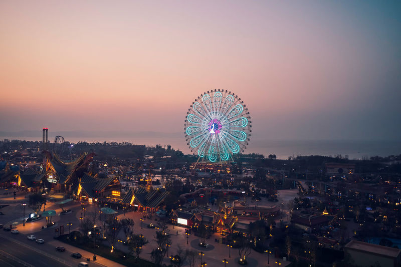 High angle view of illuminated ferris wheel against sky at sunset