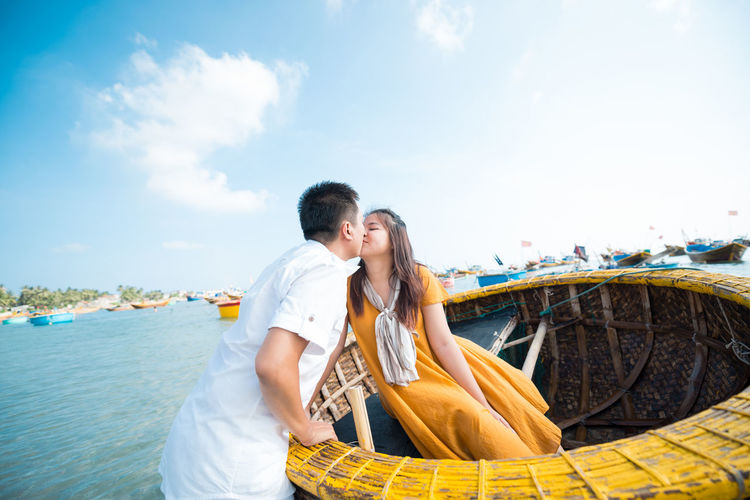Couple Kissing In Boat At Beach Against Sky
