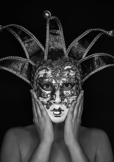 Close-up of woman wearing mask against black background