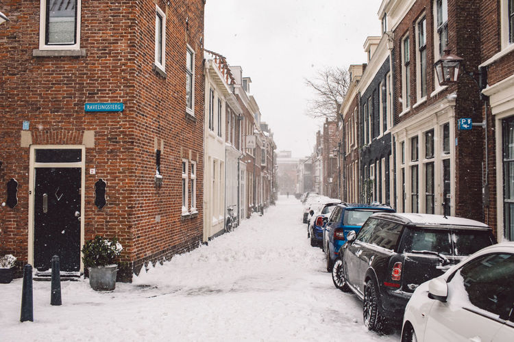 Vehicles on road amidst buildings in city during winter