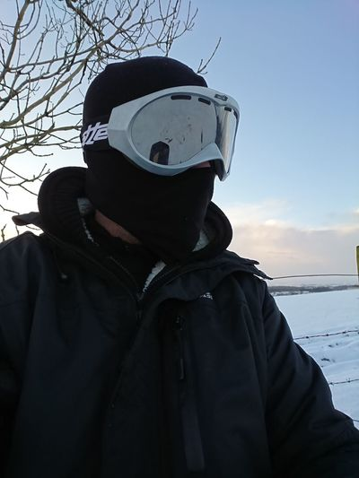 Portrait of man wearing sunglasses against sky during winter