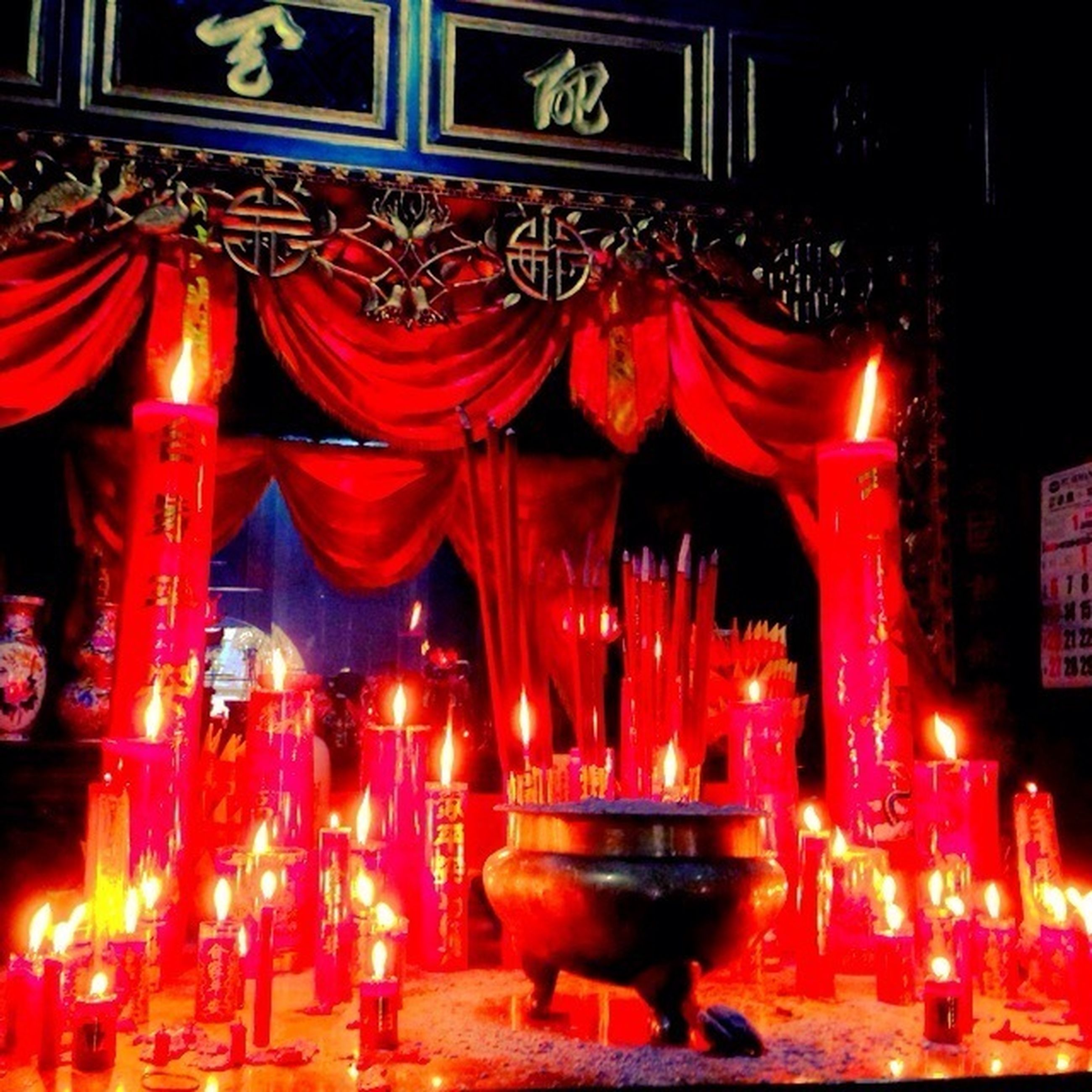 illuminated, red, night, indoors, tradition, cultures, lantern, religion, in a row, decoration, lighting equipment, art and craft, human representation, temple - building, celebration, spirituality, culture, candle, hanging, art