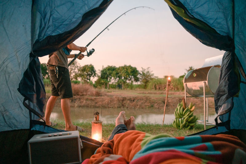 Low section of person sleeping in tent while male friend fishing against sky during sunset