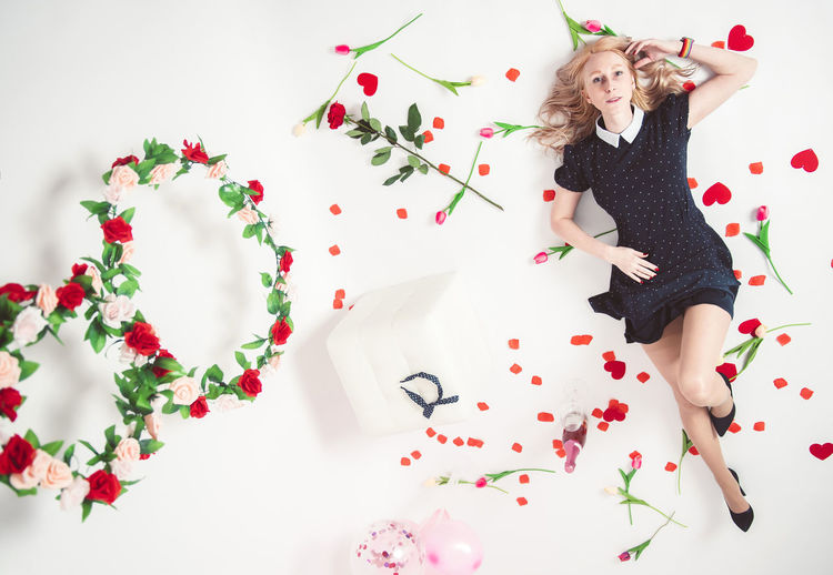 High angle view of woman with red flowers