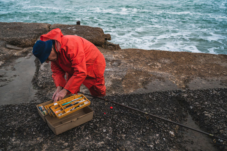 Man searching for fishing bait in container while standing by sea