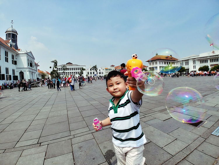 Childhood Sky Child Fun Day Multi Colored People Playing Large Group Of People Bubble Wand Full Length Crowd Building Exterior City Building Kid Architecture Historical Building Real People Outdoors Bubbles Bubble Gun Gun Toy Human Body Part Human Hand The Street Photographer - 2018 EyeEm Awards