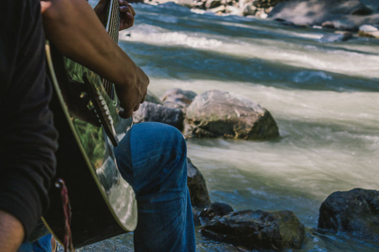 Midsection Of Guitarist With Friend At Riverbank